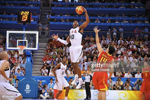 Kobe Bryant of the US Men's Senior National Team rebounds against Wang Zhizhi of China during day 2 of the men's preliminary basketball game at the...