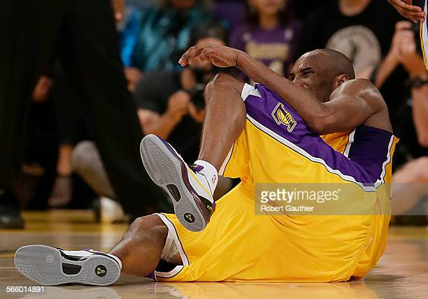 Kobe Bryant rolls on the ground in pain as he injures his achilles tendon late in the fourth quarter against the Warriors at Staples Center