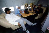 Kobe Bryant Tyronn Lue Rick Fox and Brian Shaw of the Los Angeles Lakers chat on board the Lakers' team flight back to Los Angeles the day after...