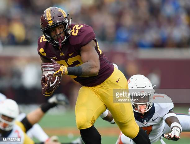 Kobe McCrary of the Minnesota Golden Gophers avoids a tackle by Stanley Green of the Illinois Fighting Illini during the first quarter of the game on...