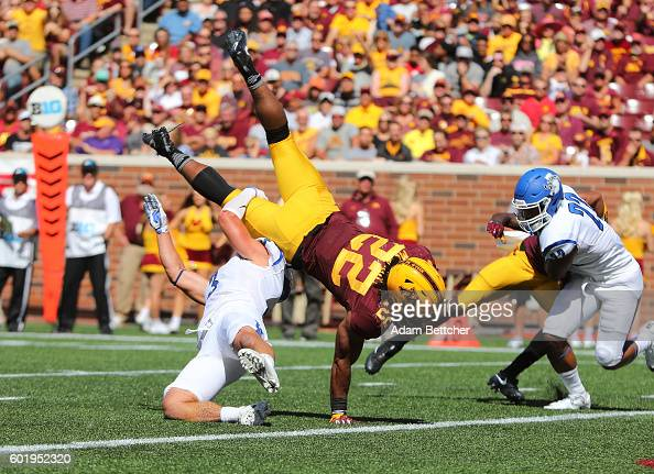 Kobe McCrary of the Minnesota Golden Gophers dives over Tsali Lough of the Indiana State Sycamores for a touchdown in the second quarter at TCFBank...
