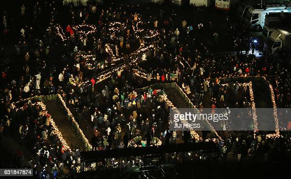 TOPSHOT Kobe residents gather around candles forming characters commemorating the 22nd anniversary of the Great Hanshin earthquake at a park in Kobe...