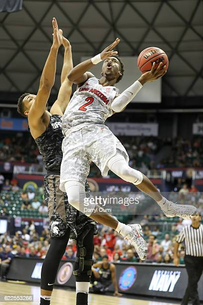 Kobi Simmons of the Arizona Wildcats leaps in the air and shoots the ball as he is defended by Kenny Goins of the Michigan State Spartans during the...