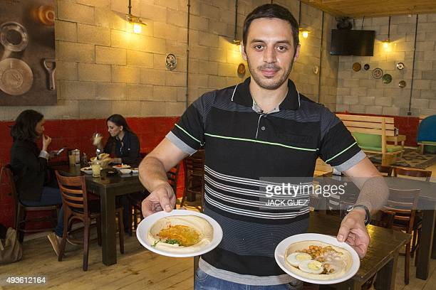 Kobi Tzafrir the owner of Hummus Bar in the central Israeli town of Kfar Vitkin displays plates of Hummus on October 21 2015 which he offers 50...