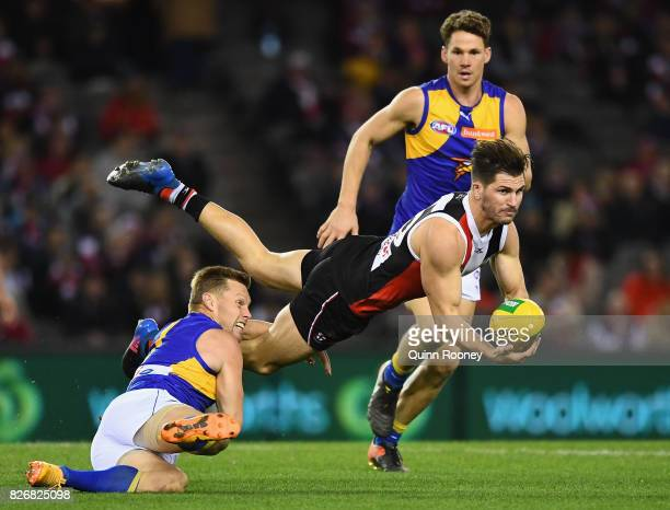 Koby Stevens of the Saints handballs whilst being tackled by Sam Mitchell of the Eagles during the round 20 AFL match between the St Kilda Saints and...