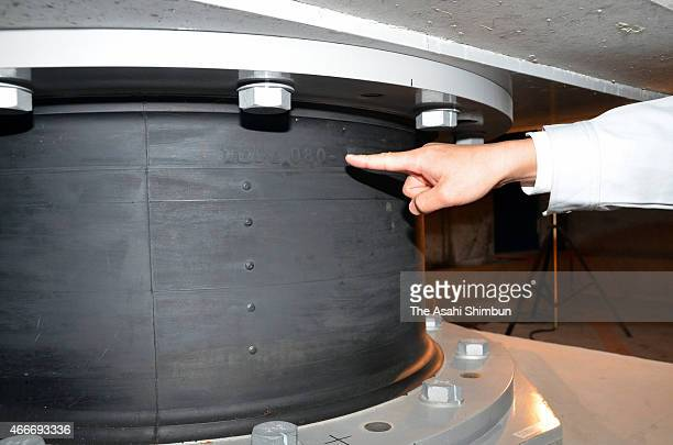 A Kochi prefecture staff checks the quakeabsorbing structures which Toyo Tire Rubber provided underneath the prefectureal headquarters main building...