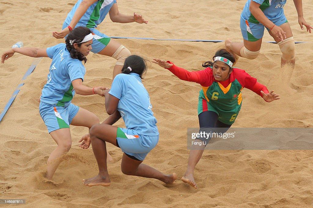 Kochi Rani Mondal (R) of Bangladesh is tackled as she competes during the Beach Kabaddi Women's Team Group A match between India and Bangladesh on Day 4 of the 3rd Asian Beach Games Haiyang 2012 at Fengxiang Beach on June 20, 2012 in Haiyang, China.