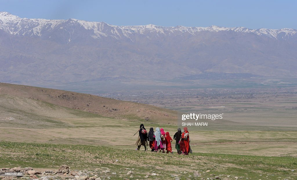 Kochi women walk in the landscape along the Kabul-Bagram road north of Kabul on April 2, 2013. Poverty and an ongoing insurgency by the ousted Taliban still pose a threat to the stability of the country. AFP PHOTO/ SHAH Marai