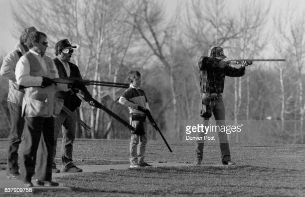 Kodacolor 100 @ 100 ASA Late afternoon sunlight Josh Olsen watches as his dad Jim far right takes aim at a flying clay pigeon at the Robert Clement...