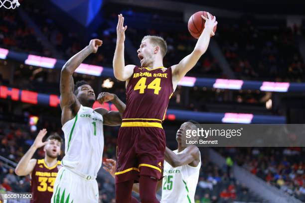 Kodi Justice of the Arizona State Sun Devils handles the ball against Jordan Bell and Chris Boucher of the Oregon Ducks during a quarterfinal game of...