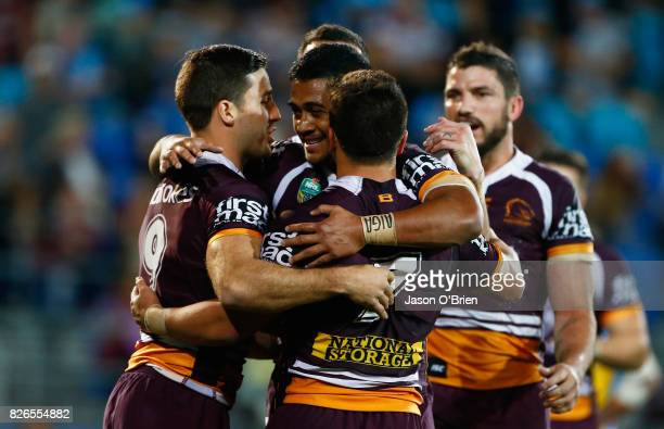 Kodi Nikorima of the Broncos is congratulated by team mates after scoring a try during the round 22 NRL match between the Gold Coast Titans and the...