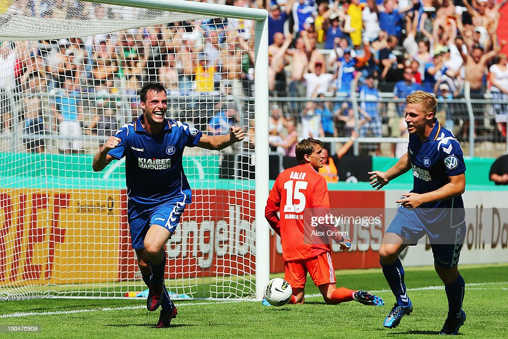 Koen van der Biezen (L) of Karlsruhe celebrates his team's first goal with team mate <a gi-track='captionPersonalityLinkClicked' href=/galleries/search?phrase=Rouwen+Hennings&family=editorial&specificpeople=613041 ng-click='$event.stopPropagation()'>Rouwen Hennings</a> as goalkeeper <a gi-track='captionPersonalityLinkClicked' href=/galleries/search?phrase=Rene+Adler&family=editorial&specificpeople=686184 ng-click='$event.stopPropagation()'>Rene Adler</a> of Hamburg reacts during the first round match of the DFB Cup between Karlsruher SC and Hamburger SV at Wildpark Stadium on August 19, 2012 in Karlsruhe, Germany.