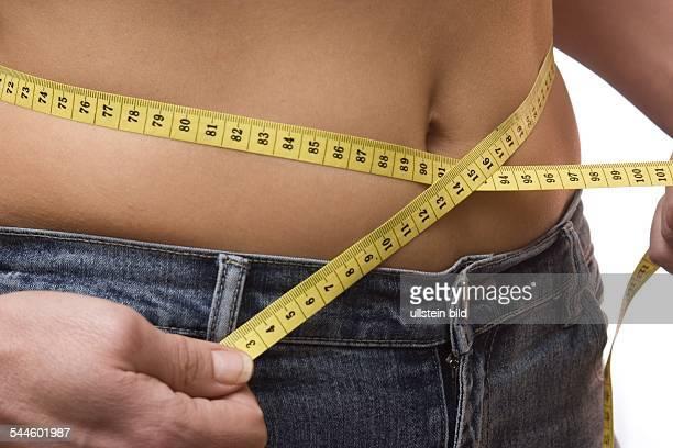 Koerpergewicht Diaet Frau misst Bauchumfang mit einem Massband