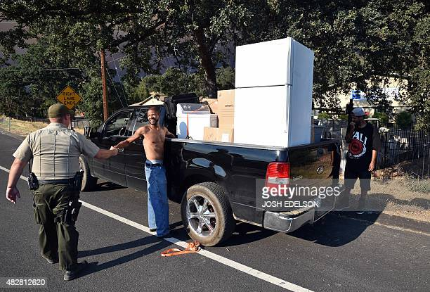 Kofawn Jones shakes hands with a police officer while preparing to evacuate as the Rocky fire approaches his home in Clearlake California on August 2...