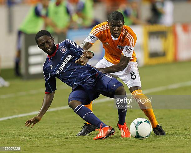 Kofi Sarkodie of Houston Dynamo pushes Patrick Nyarko of Chicago Fire aside as he goes for the ball at BBVA Compass Stadium on July 27 2013 in...