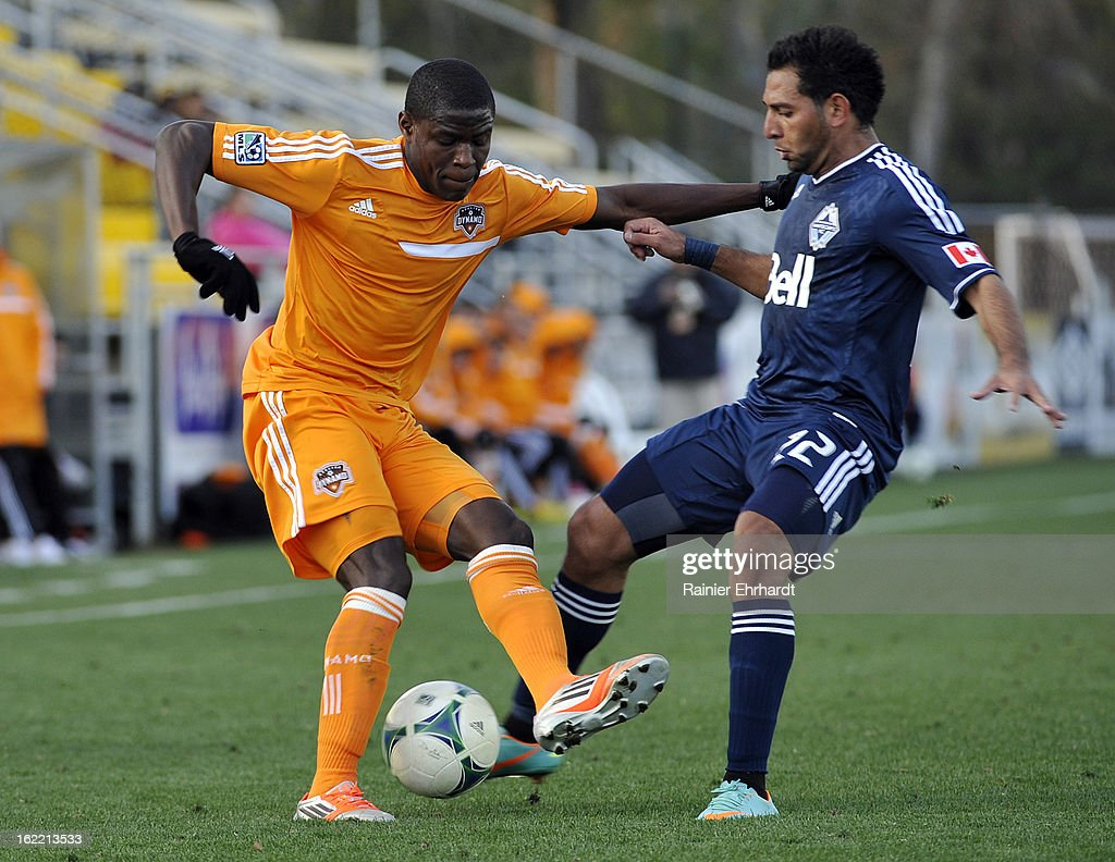 Kofi Sarkodie #8 of the Houston Dynamo and Paul Araujo Jr. #22 of the Vancouver Whitecaps FC battle for the ball during the first half of a game on February 20, 2013 in Charleston, North Carolina.