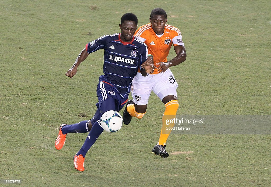 Kofi Sarkodie#8 of the Houston Dynamo battles for the ball against Patrick Nyarko #14 of the Chicago Fire at BBVA Compass Stadium on July 27, 2013 in Houston, Texas.