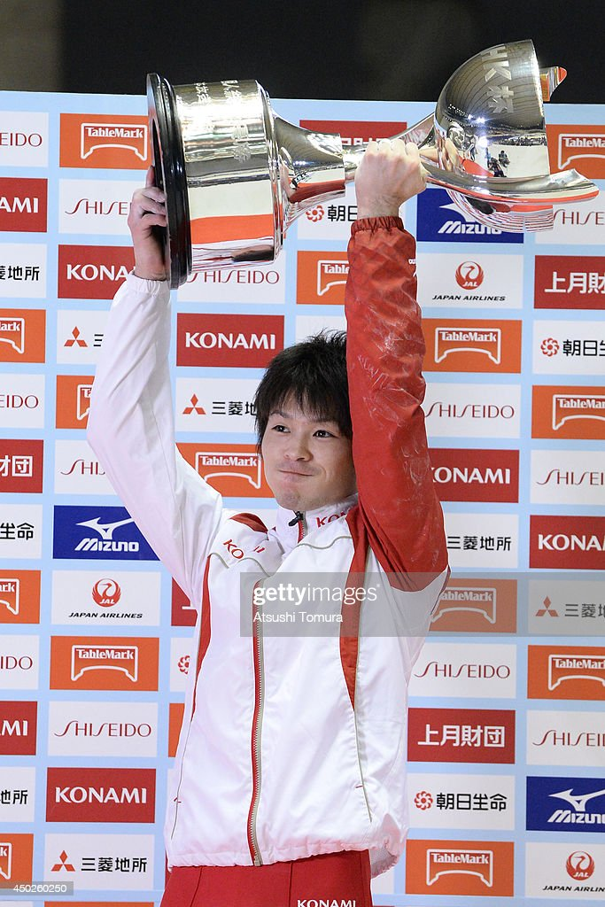Kohei Uchimura of Japan smiles as he celebrates with the NHK trophy on the podium during day two of the Artistic Gymnastics NHK Trophy at Yoyogi National Gymnasium on June 8, 2014 in Tokyo, Japan.