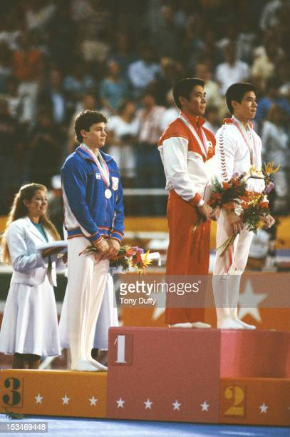 Koji Gushiken of Japan and Li Ning of China stand with their gold medals for the Men's Rings event with bronze medallist Mitch Gaylord of the United...