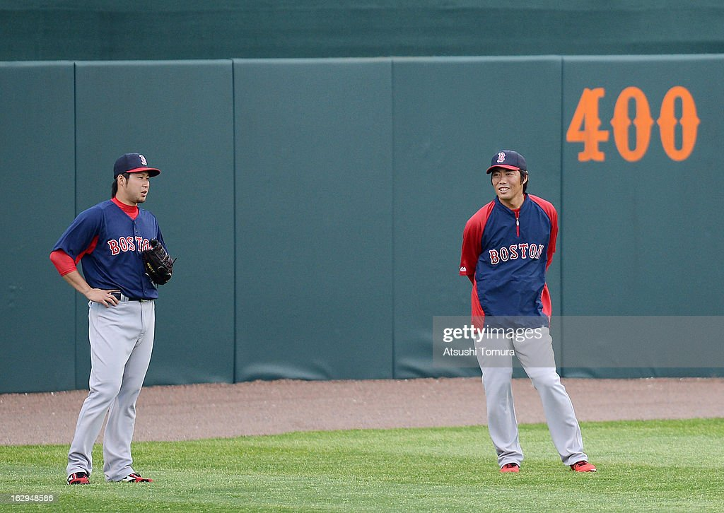 Koji Uehara (R) #19 and Junichi Tazawa #36 of Boston Red Sox warms up prior to the spring training game against Baltimore Orioles at Ed Smith Stadium on February 27, 2013 in Sarasota, Florida.