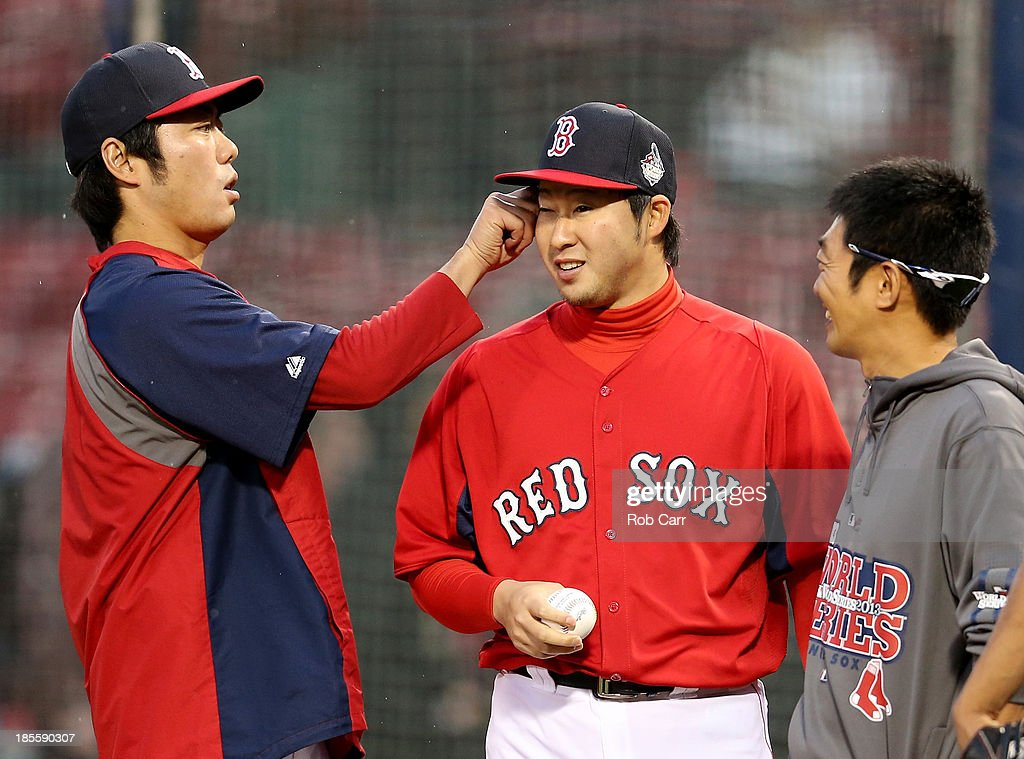 Koji Uehara (L) #19 jokes around with teammate Junichi Tazawa (C) #36 of the Boston Red Sox throws the ball during team workout in the 2013 World Series Media Day at Fenway Park on October 22, 2013 in Boston, Massachusetts. The Red Sox host the Cardinals in Game 1 on October 23, 2013.