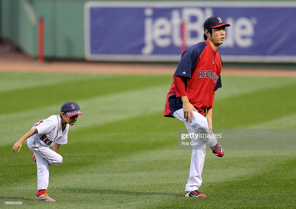 Koji Uehara (R) #19 of the Boston Red Sox warms up with his son Kazuma during team workout in the 2013 World Series Media Day at Fenway Park on October 22, 2013 in Boston, Massachusetts. The Red Sox host the Cardinals in Game 1 on October 23, 2013.
