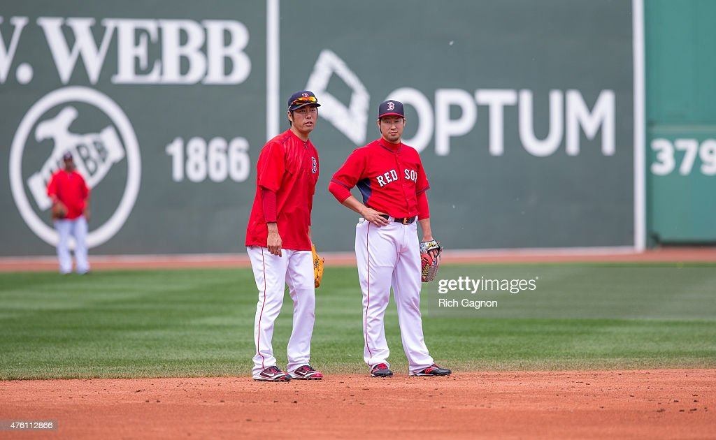 Koji Uehara #19 of the Boston Red Sox and teammate Junichi Tazawa #36 talk during batting practice before a game against the Oakland Athletics at Fenway Park on June 6, 2015 in Boston, Massachusetts.