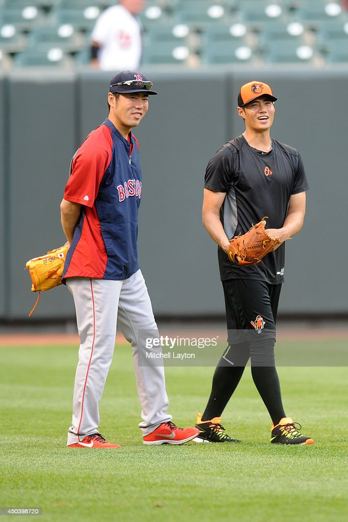Koji Uehara #19 of the Boston Red Sox and Wei-Yin Chen #16 of the Baltimore Orioles talk in the outfield before a baseball game on June 10, 2014 at Oriole Park at Camden Yards in Baltimore, Maryland.