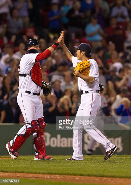 Koji Uehara of the Boston Red Sox celebrates a victory with teammate AJ Pierzynski after the ninth inning against the Minnesota Twins at Fenway Park...