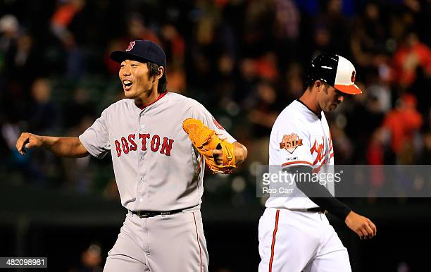 Koji Uehara of the Boston Red Sox celebrates in front of JJ Hardy of the Baltimore Orioles following the Red Sox 62 win at Oriole Park at Camden...