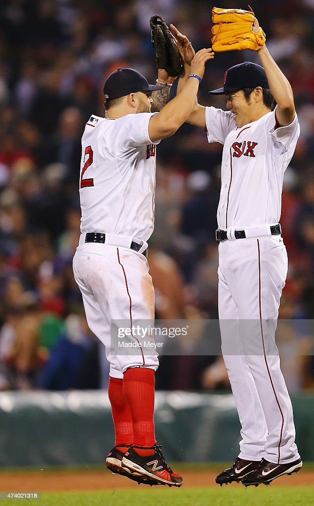 Koji Uehara of the Boston Red Sox celebrates with Mike Napoli after defeating the Texas Rangers 43 at Fenway Park on May 19 2015 in Boston...