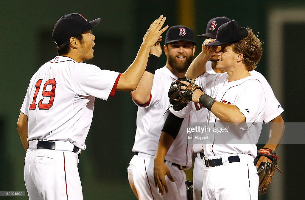 Koji Uehara #19 of the Boston Red Sox celebrates with Mike Napoli #12 and Brock Holt #26 after defeating the Kansas City Royals, 2-1, at Fenway Park on July 19, 2014 in Boston, Massachusetts.