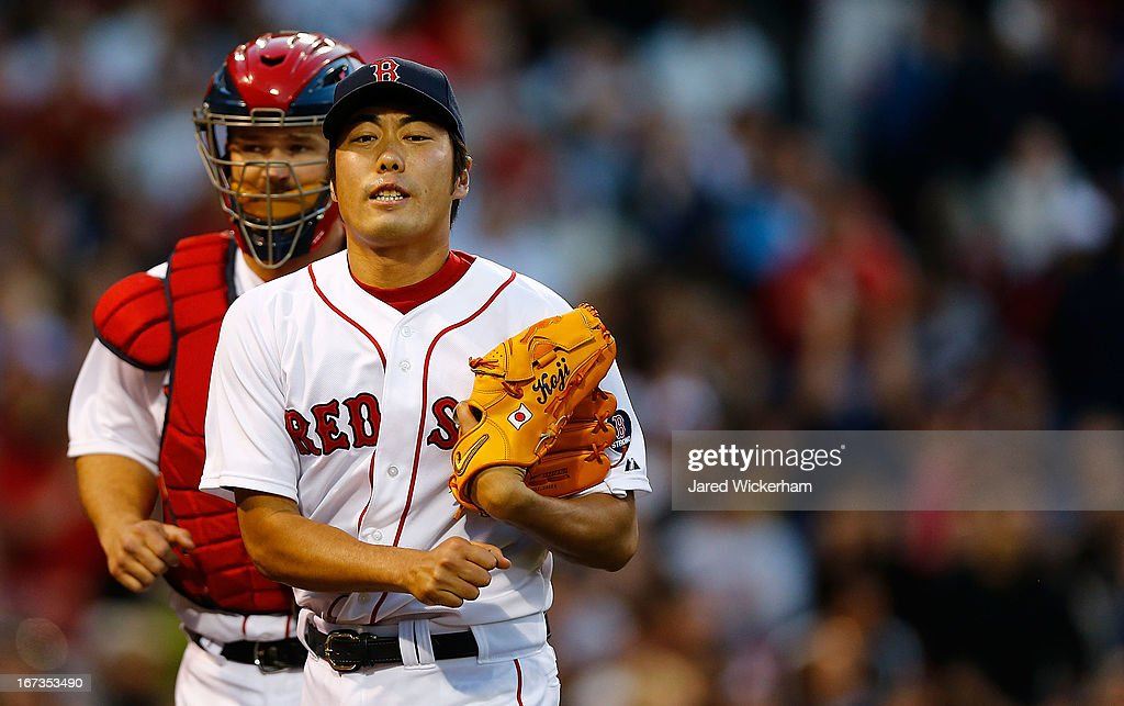 Koji Uehara #19 of the Boston Red Sox celebrates with teammate David Ross #3 of the Boston Red Sox after getting out of the inning during the game on April 24, 2013 at Fenway Park in Boston, Massachusetts.