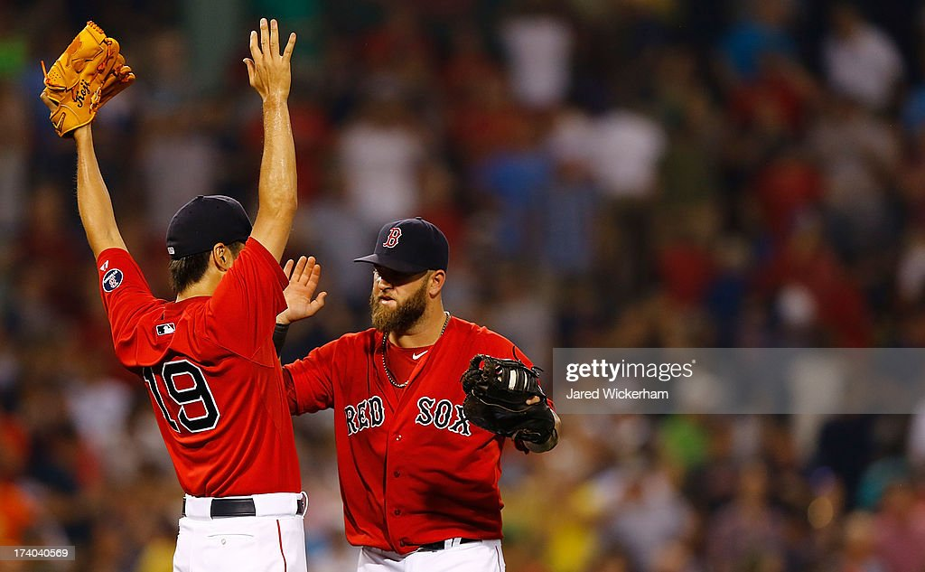 Koji Uehara #19 of the Boston Red Sox celebrates with teammate Mike Napoli #12 after closing out the 9th inning against the New York Yankees during the game on July 19, 2013 at Fenway Park in Boston, Massachusetts.