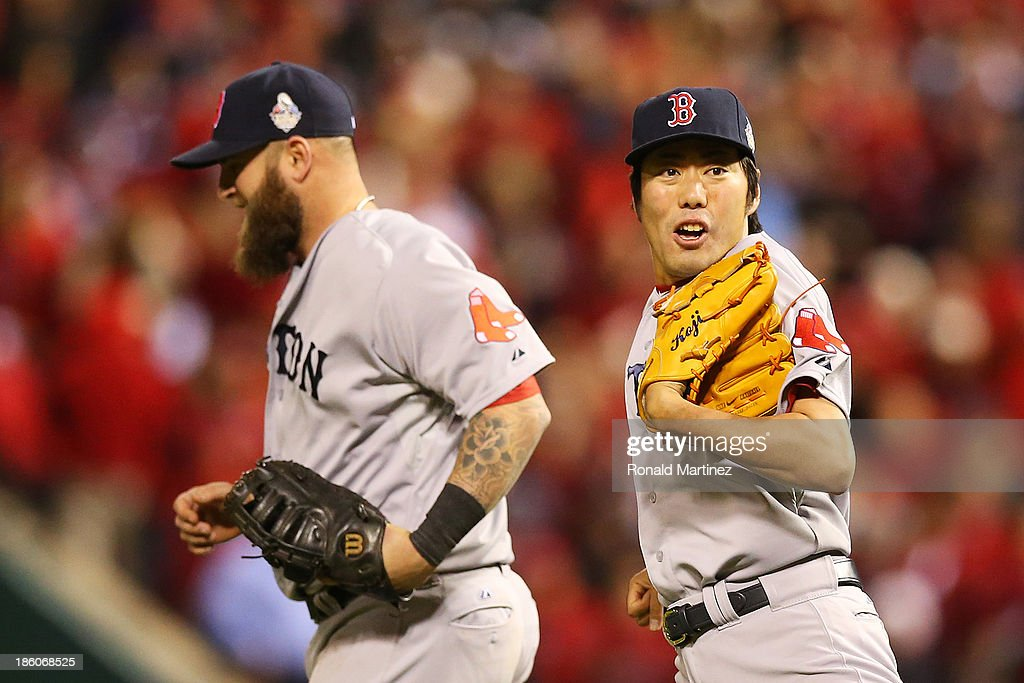 Koji Uehara of the Boston Red Sox celebrates with teammate Mike Napoli after defeating the St Louis Cardinals in Game Four of the 2013 World Series...