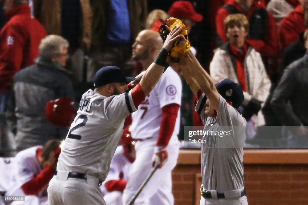 Koji Uehara of the Boston Red Sox celebrates with teammate Mike Napoli after throwing out Kolten Wong of the St Louis Cardinals to win Game Four of...