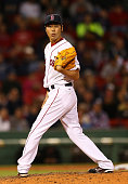 Koji Uehara of the Boston Red Sox checks the runner at first base in the ninth inning against the Los Angeles Angels at Fenway Park on May 23 2015 in...