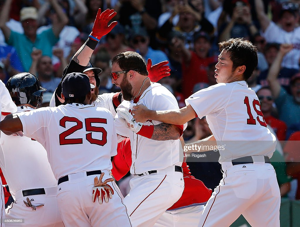 Koji Uehara #19 of the Boston Red Sox grabs Mike Napoli #12 of the Boston Red Sox who connected for a game-winning walk off home run against Minnesota Twins in the 10th inning at Fenway Park on June 18, 2014 in Boston, Massachusetts.