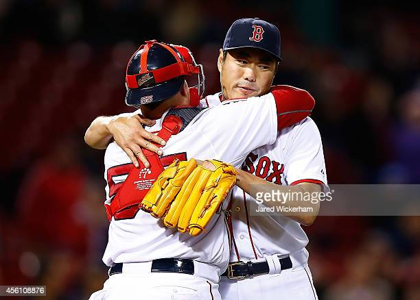 Koji Uehara of the Boston Red Sox hugs teammate Christian Vazquez following his save in the 9th inning against the Tampa Bay Rays during the game at...