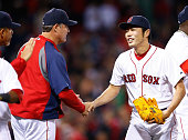 Koji Uehara of the Boston Red Sox is congratulated on the 43 win by manager John Farrell against the Cincinnati Reds in the 9th inning during the...