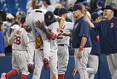 Koji Uehara of the Boston Red Sox is lifted by David Ortiz as manager John Farrell and pitching coach Carl Willis wait for them to celebrate their...