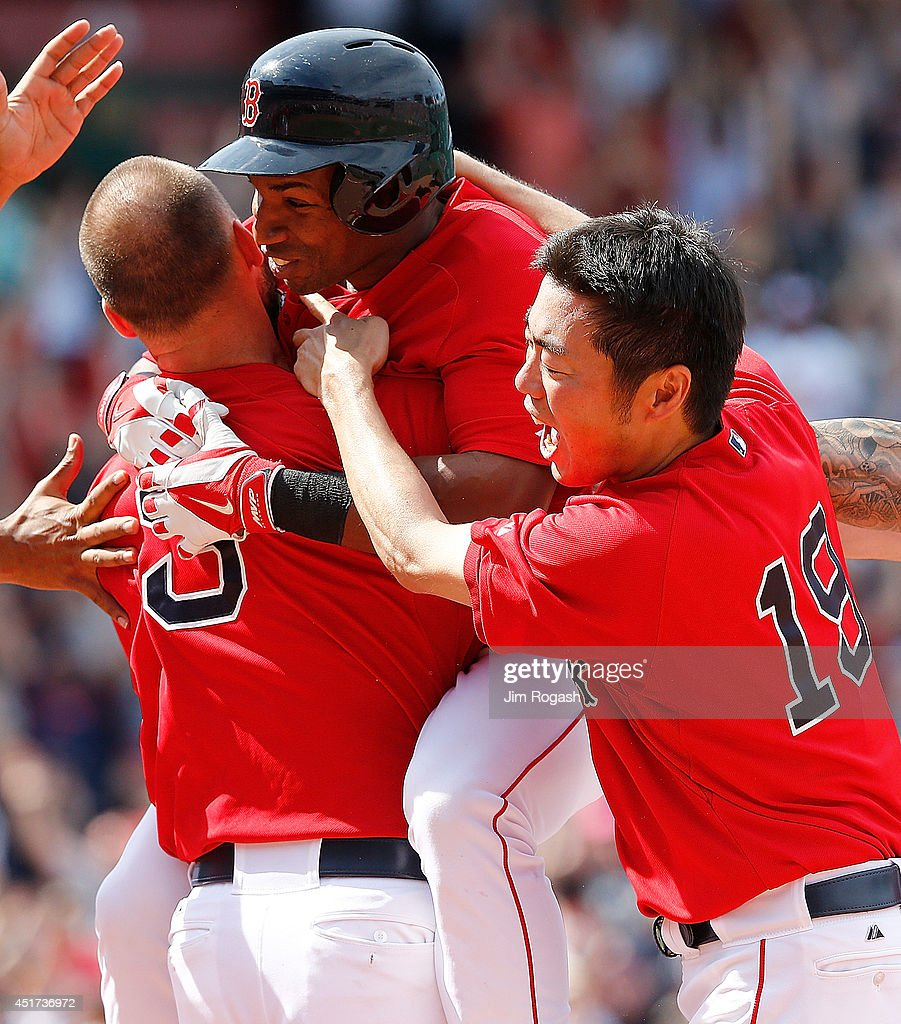Koji Uehara of the Boston Red Sox jumps on Jonathan Herrera of the Boston Red Sox after he singled in the winning run in the ninth inning during the...