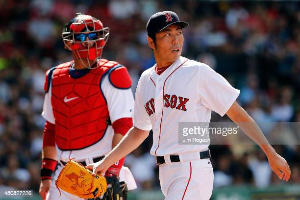 Koji Uehara of the Boston Red Sox leaves the field with AJ Pierzynski after hegave up a home run to Chris Parmelee of the Minnesota Twins in the 10th...