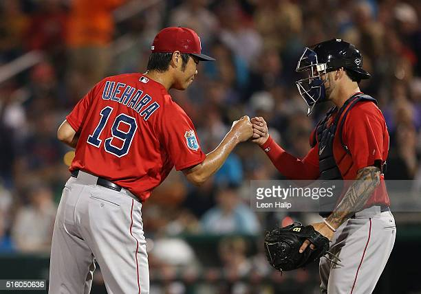 Koji Uehara of the Boston Red Sox leaves the game in the fifth inning and bumps fists with catcher Blake Swihart during the Spring Training Game on...