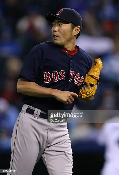 Koji Uehara of the Boston Red Sox looks at the scoreboard after pitching in the eighth inning against the Kansas City Royals at Kauffman Stadium on...