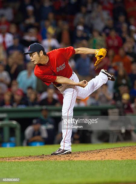 Koji Uehara of the Boston Red Sox pitching as he gave up 5 runs during the ninth inning against the Seattle Mariners at Fenway Park after leading 30...