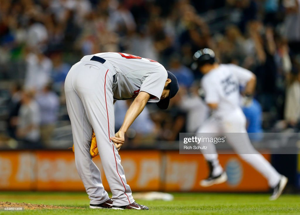 Koji Uehara #19 of the Boston Red Sox reacts after giving up a game tying homerun to Mark Teixeira #25 of the New York Yankees who round first base during the ninth inning in a MLB baseball game at Yankee Stadium on September 4, 2014 in the Bronx borough of New York City.