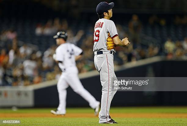 Koji Uehara of the Boston Red Sox rubs the ball as Brian McCann of the New York Yankees circles the bases after hitting a home run during the ninth...