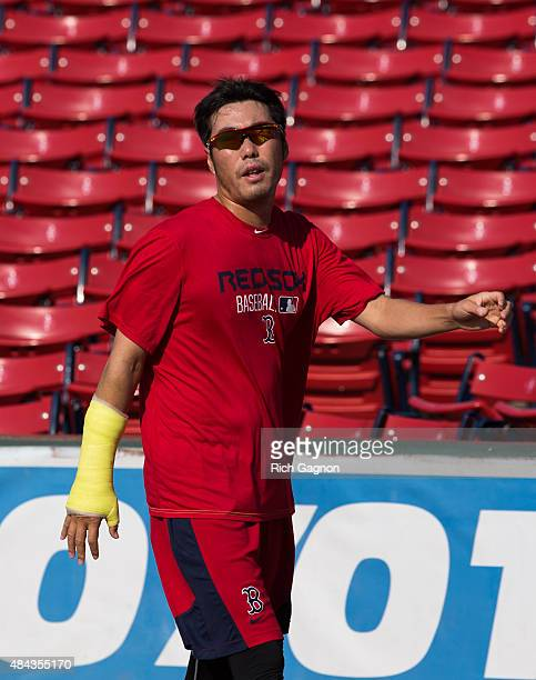 Koji Uehara of the Boston Red Sox runs around the outfield with a cast on his right wrist before a game against the Cleveland Indians on August 17...