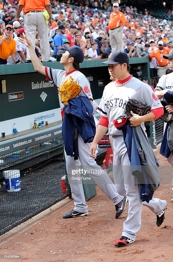 <a gi-track='captionPersonalityLinkClicked' href=/galleries/search?phrase=Koji+Uehara&family=editorial&specificpeople=801278 ng-click='$event.stopPropagation()'>Koji Uehara</a> #19 of the Boston Red Sox tosses a ball to a fan after a 5-0 victory against the Baltimore Orioles at Oriole Park at Camden Yards on July 28, 2013 in Baltimore, Maryland.